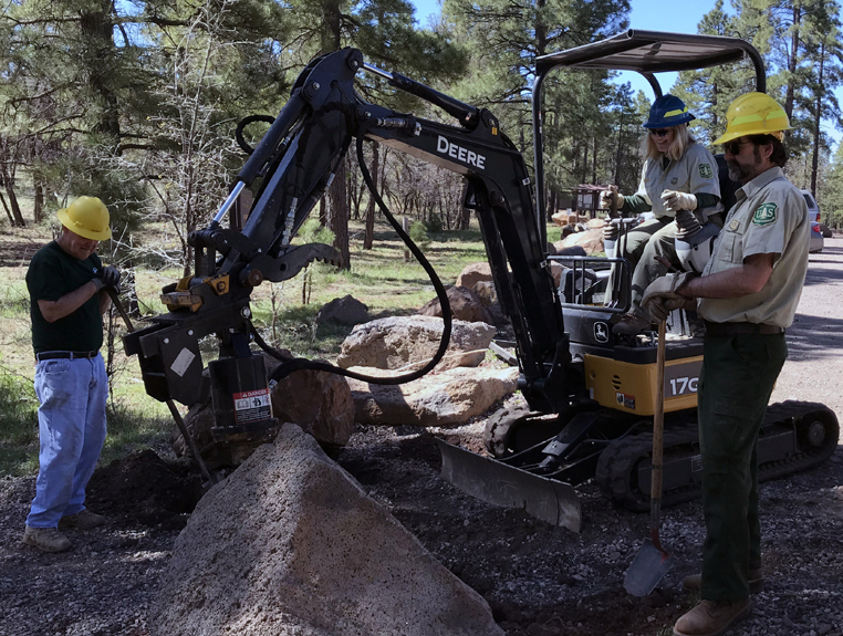 Work crew uses heavy equipment to install trail gate