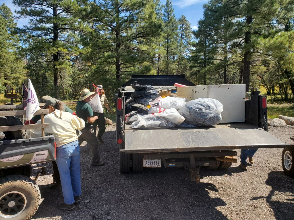 Loading trash into Forest Service truck for delivery to dump.